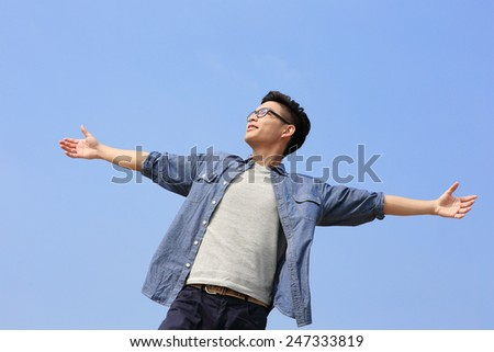 Carefree and free man raised hands and looking to a sky, asian - stock photo