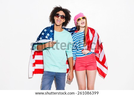 Carefree and in love. Funky young couple covering with American flag and smiling while standing against white background - stock photo