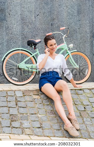 Carefree and stylish. Beautiful young smiling woman talking on the mobile phone while sitting at the roadside near her vintage bicycle - stock photo