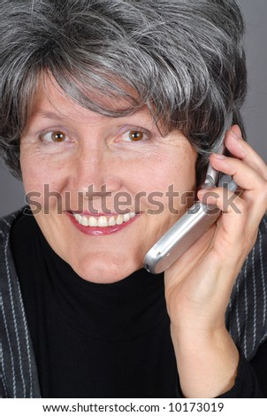 Carefree attractive older woman talking on the cell phone - stock photo
