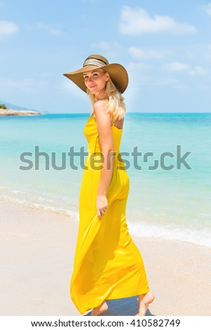 Carefree beautiful fashion blonde woman in beach straw hat and long yellow dress flying in the wind walking barefoot by sand of tropical beach. Natural woman beauty. Lady go away and turned to camera. - stock photo