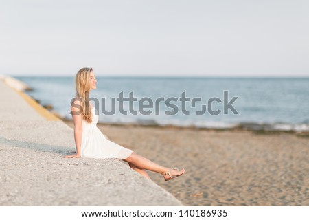 Carefree beautiful young blond woman relaxing at the seaside sitting on a stone wall kicking her bare feet in the air - stock photo