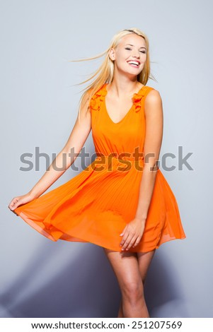 Carefree beauty. Beautiful young woman in pretty dress posing and smiling while standing against grey background   - stock photo
