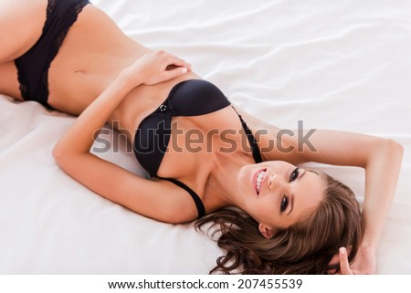 Carefree beauty in bed. Top view of beautiful young brown hair woman in black lingerie lying in bed and smiling to you  - stock photo