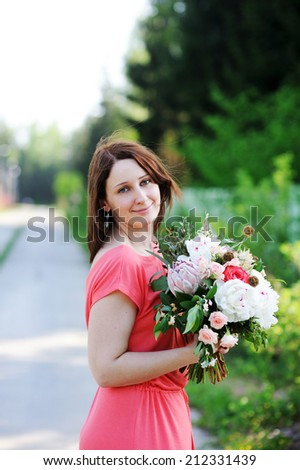 Carefree beauty woman with flowers outdoor in the summer evening - stock photo