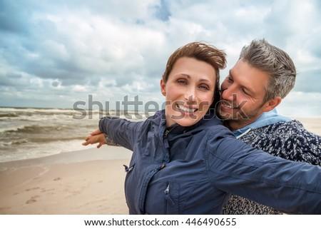 carefree boyfriend with girlfriend on windy coast - stock photo