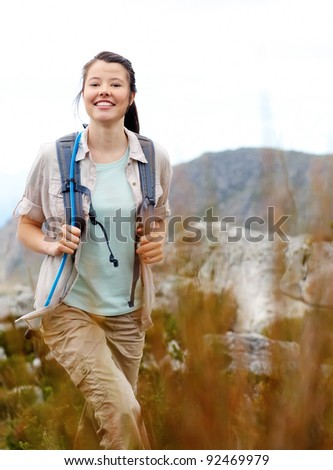 Carefree brunette girl walks outdoors hiking and exploring. she is cheerful and happy