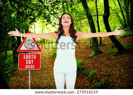 Carefree brunette with arms out against peaceful autumn scene in forest - stock photo