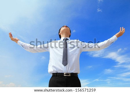 carefree business man arms up and looking to empty copy space isolated on blue sky background, asian model - stock photo
