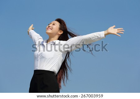 carefree business woman arms up and feel free isolated on blue sky background, asian beauty - stock photo