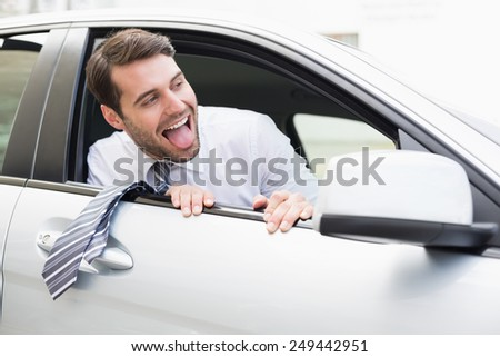Carefree businessman sitting in drivers seat in his car - stock photo