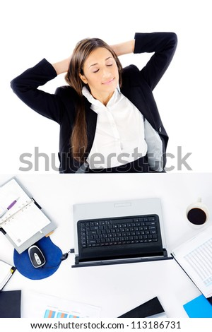 Carefree businesswoman is relaxing at her desk with arms behind her head and daydreaming