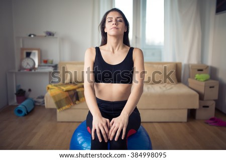 Carefree calm woman meditating.Enjoying peace and serenity.Living room for after work relaxation and meditation.Having a deep breath.After work out relaxation of muscles and breathing exercises - stock photo