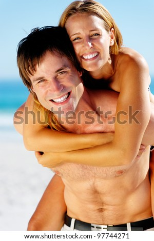 carefree couple embrace and enjoy some summer beach loving on a tropical island - stock photo
