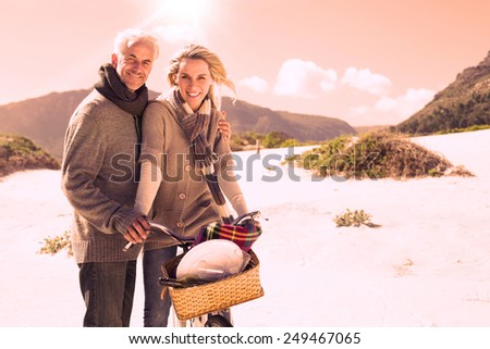 Carefree couple going on a bike ride and picnic on the beach on a bright but cool day - stock photo