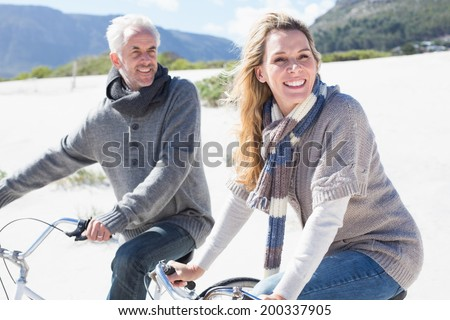 Carefree couple going on a bike ride on the beach on a bright but cool day - stock photo