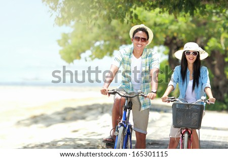 carefree couple having fun and smiling riding bicycle at the beach - stock photo
