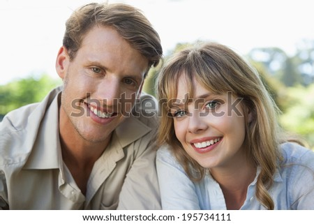 Carefree couple lying in the park smiling at camera on a sunny day - stock photo