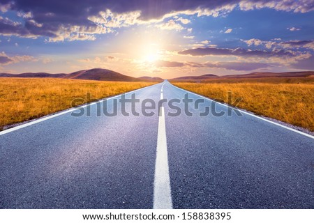 Carefree driving on an empty road at sunset - stock photo