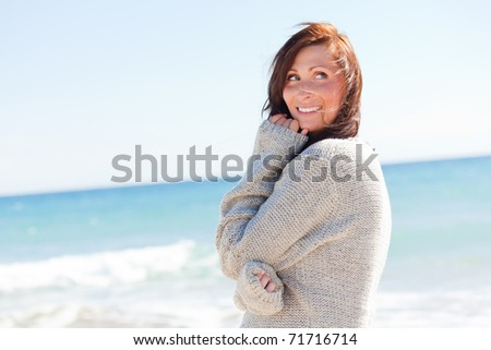 Carefree female walking down the coastline with hands in hair - stock photo