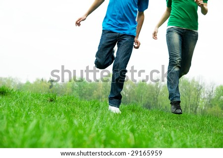 Carefree friends running together on green meadow - stock photo