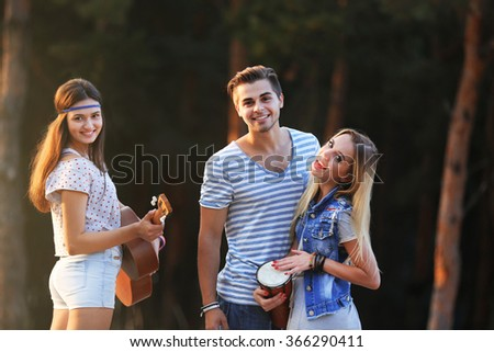 Carefree friends with guitar and drum, outdoors - stock photo
