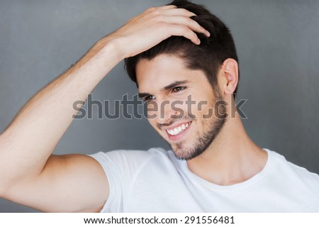 Carefree handsome. Happy young man holding hand in hair and looking away while standing against grey background - stock photo