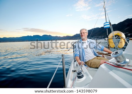 carefree happy sailing man portrait of mature retired man on ocean boat at sunrise - stock photo