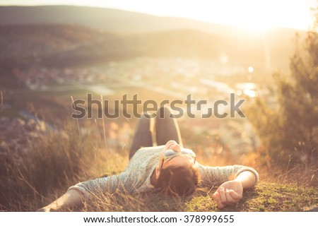 Carefree happy woman lying on green grass meadow on top of mountain edge cliff enjoying sun on her face.Enjoying nature sunset.Freedom.Enjoyment.Relaxing in mountains at sunrise.Sunshine.Daydreaming - stock photo