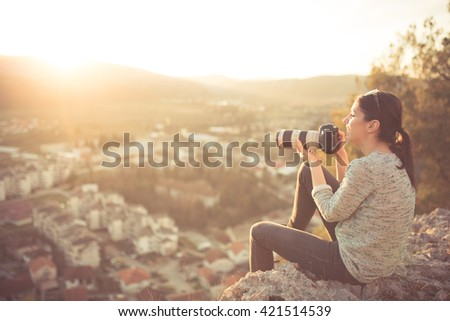 Carefree happy woman sitting on top of mountain edge cliff enjoying sun on her face and photographing sunset. Enjoying nature sunset. Freedom. Enjoyment. Relaxing in mountains at sunrise. Daydreaming - stock photo