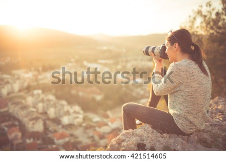 Carefree happy woman sitting on top of mountain edge cliff enjoying sun on her face and photographing sunset.Enjoying nature sunset.Freedom.Enjoyment.Relaxing in mountains at sunrise.Daydreaming - stock photo