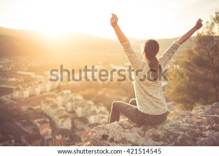 Carefree happy woman sitting on top of mountain edge cliff enjoying sun on her face raising hands in sunlight rays.Enjoying nature sunset.Freedom.Enjoyment.Relaxing in mountains at sunrise.Daydreaming - stock photo