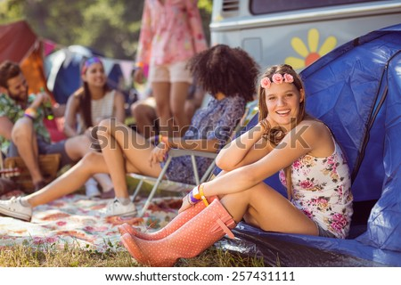 Carefree hipster smiling on campsite at a music festival - stock photo