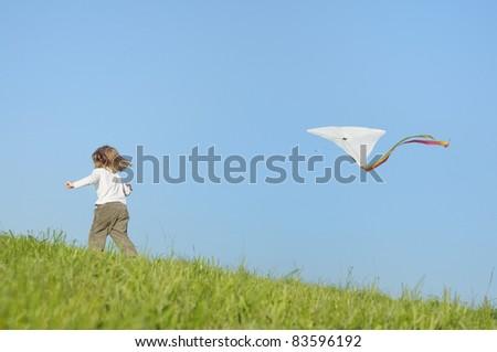 carefree kid girl enjoying childhood playing with kite - stock photo