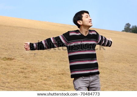 Carefree man standing in golden grass field being happy enjoying freetime - stock photo