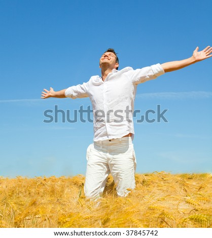 Carefree man standing in golden wheat field being happy enjoying freetime - stock photo