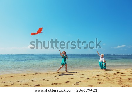 Carefree mother having a fun running with flying red kite on sea beach to baby girl and grandmother. Three generations of family, happy parenting and active leisure during summer vacation with child - stock photo