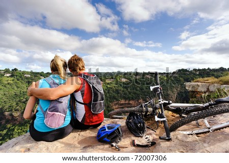 carefree mountain bike couple sit together and hug - stock photo