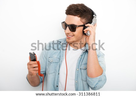 Carefree music lover. Joyful young man in headphones smiling and looking at smart phone while standing against white background