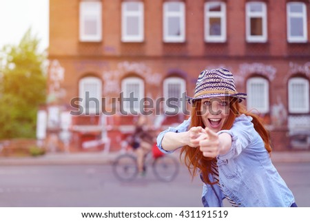 Carefree playful young redhead woman in a trendy outfit stretching forwards pointing at the camera with wide eyes and a wide grin - stock photo