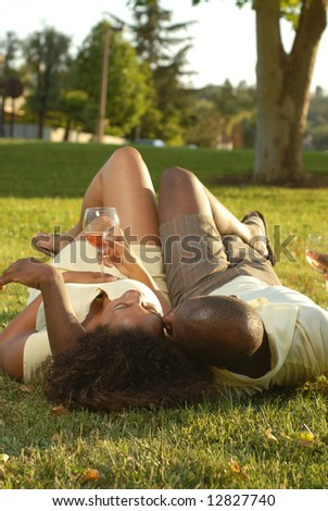 Carefree, relaxed couple enjoying the sunshine with a mellow drink of wine - stock photo