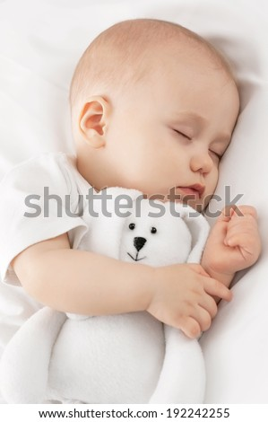 Carefree sleep little baby with a soft toy on the bed - stock photo