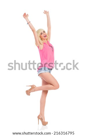 Carefree slim girl. Smiling blond young woman in high heels and pink top standing on one leg with arms raised. Full length studio shot isolated on white. - stock photo