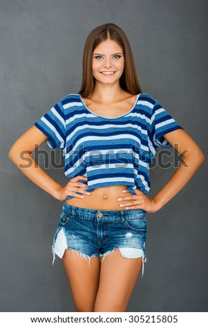 Carefree style. Cheerful young woman looking at camera and holding hands on hips while standing against grey background   - stock photo