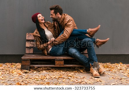 Carefree time together. Beautiful young couple having fun together while sitting on the wooden pallet together with grey wall in the background and fallen leaves on ht floor - stock photo