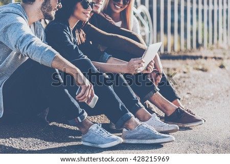 Carefree time with best friends. Close-up of group of young smiling people bonding to each other and looking at digital tablet while sitting outdoors together - stock photo