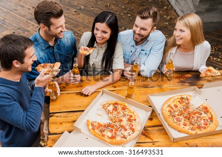 Carefree time with friends. Top view of five cheerful peopleholding bottles with beer and eating pizza while standing outdoors - stock photo