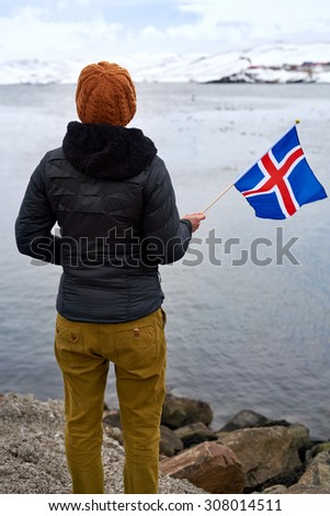 Carefree tourist enjoying the scenary scenic view across the water towards the mountains while waving iceland flag - stock photo