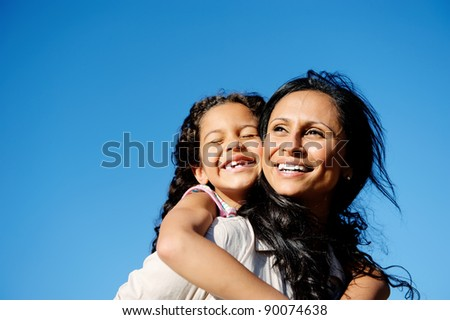 carefree vitality image of mother and daughter playing together outdoors - stock photo