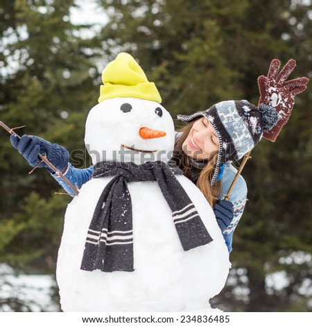 Carefree winter funny young woman with snowman  - stock photo